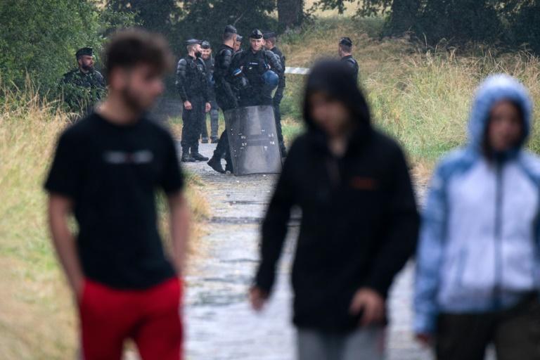 Des teufeurs passent devant les forces de l'ordre dans un champ près du lieu de la rave-party illégale organisée à Redon, en Ille-et-Vilaine, le 19 juin 2021
