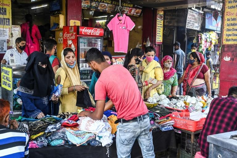 Des gens font leurs emplettes dans un marché bondé à New Delhi le 16 juin 2021 après l'assouplissement des restrictions anti-Covid.