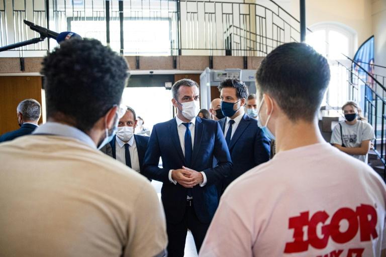 Le ministre français de la Santé, Olivier Véran (c) discute avec des jeunes alors qu'il visite un centre de vaccination à Paris, le 15 juin 2021