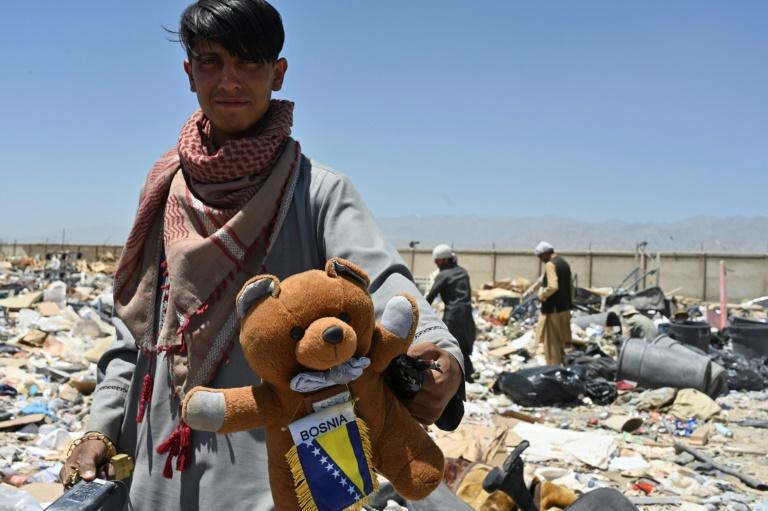 Un homme montre un ours en peluche trouvé dans des déchets près de la base américaine de Bagram, en cours d'évacuation en Afghanistan, le 17 juin 2021