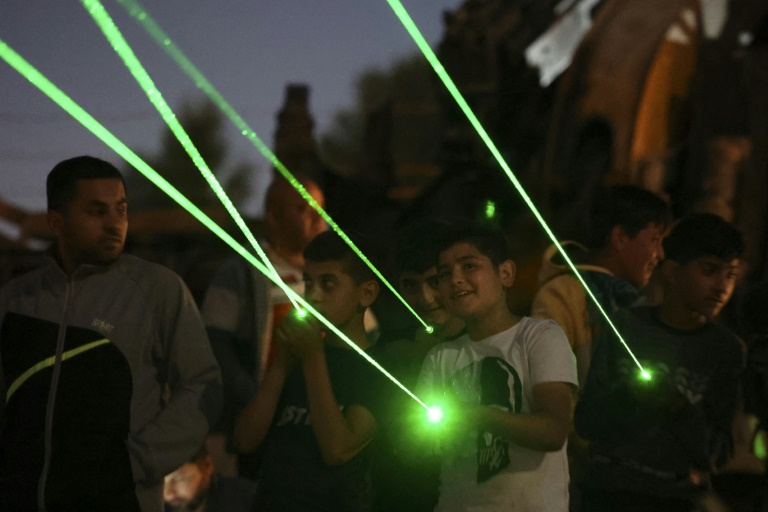 Des manifestants palestiniens à Beita en Cisjordanie projettent des rayons lasers verts vers la colonie Eviatar, installée sur une colline, le 23 juin 2021