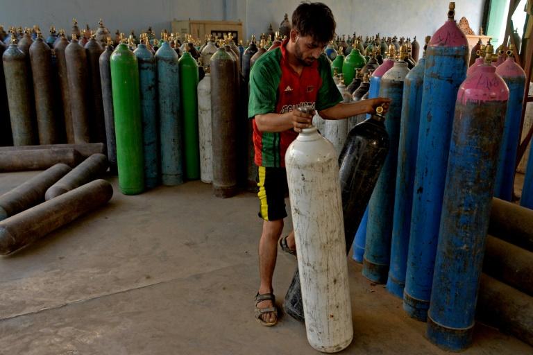 Un employé manipule des bombonnes d'oxygène destinées aux malades du covid le 11 juin 2021 à Jalalabad (Afghanistan)