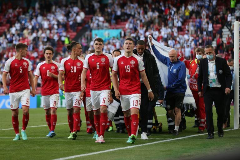 Les joueurs danois escortent l'équipe médicale qui évacue sur une civière Christian Eriksen après son malaise cardiaque contre la Finlande le 12 juin 2021 à Copenhague
