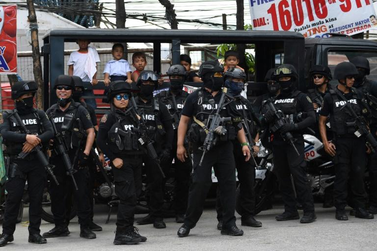 Des membres des forces de l'ordre escortent des