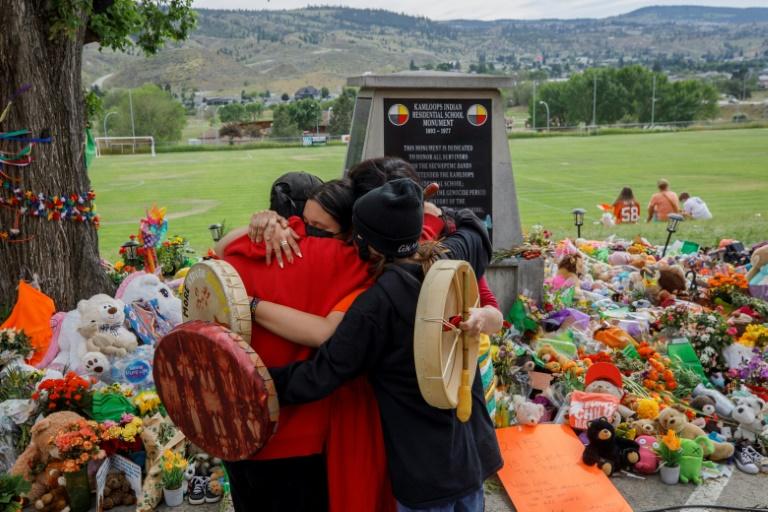 Des membres de la nation Mosakahiken Cree s'enlacent devant un mémorial aux 215 enfants autochtones dont les restes ont été trouvés près d'un pensionnat, le 4 juin 2021 à Kamloops, au Canada