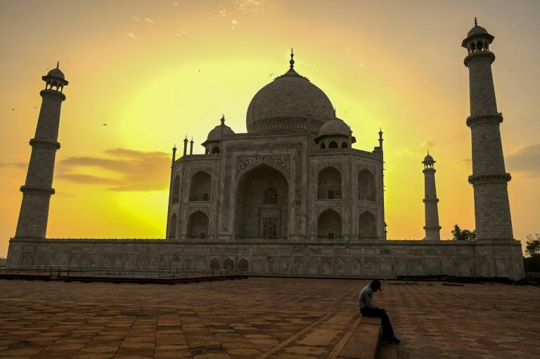 Un gardien du Taj Mahal se repose au lever du soleil le 16 juin 2021, jour de la réouverture de ce monument à Agra en Inde