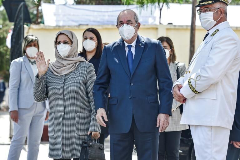 Le président algérien Abdelmadjid Tebboune (C) arrive avec son épouse (G) à un bureau de vote en banlieue d'Alger, le 12 juin 2021