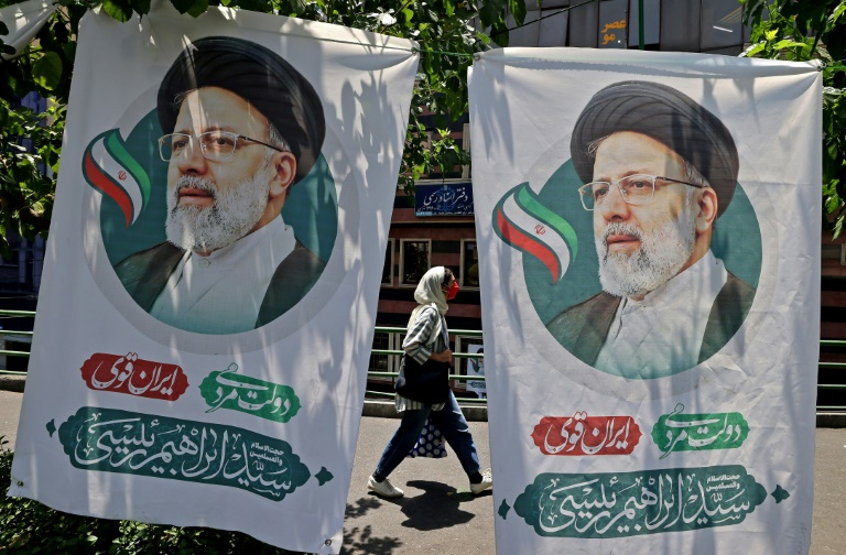 Une Iranienne passe entre deux affiches du candidat à la présidentielle Ebrahim Raisi, à Téhéran le 17 juin 2021