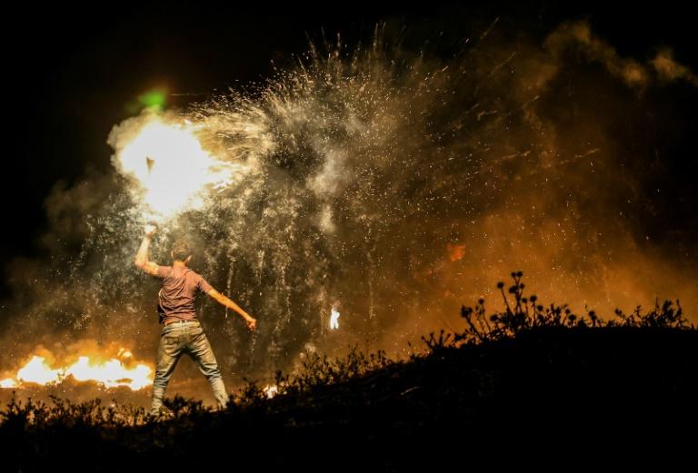 Un Palestinien lance un projectile en destination des forces israéliennes lors d'une manifestation à l'est de Gaza le 15 juin 2021