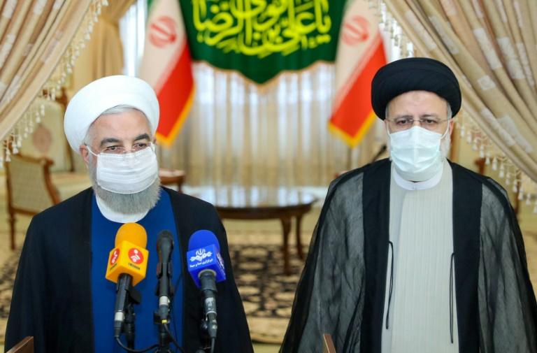 Le président iranien sortant Hassan Rohani (g) et le nouveau président élu Ebrahim Raïssi, lors d'une conférence de presse, le 19 juin 2021 à Téhéran