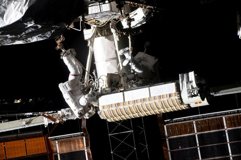 L'astronaute français Thomas Pesquet (G) installe un panneau solaire sur la Station spatiale internationale, le 20 juin 2021