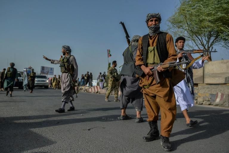 Des forces de sécurité afghanes et des miliciens anti-taliban montent la garde dans une rue d'Enjil, dans la province d'Herat, le 30 juillet 2021.