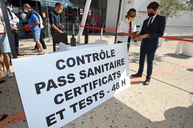 Le porte-parole du gouvernement Gabriel Attal (D) présente son pass sanitaire lors d'une visite dans un cinéma de Montpellier le 29 juillet 2021