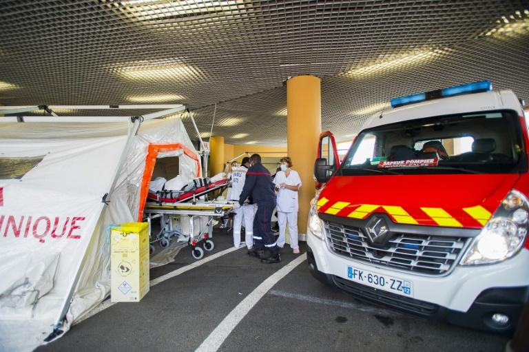 Des pompiers transportent un patient atteint du Covid-19 sur une civière à l'intérieur d'une tente de triage à l'extérieur de l'hôpital universitaire Pierre Zobda-Quitman University hospital (CHU) à Fort-de-France le 30 juillet 2021