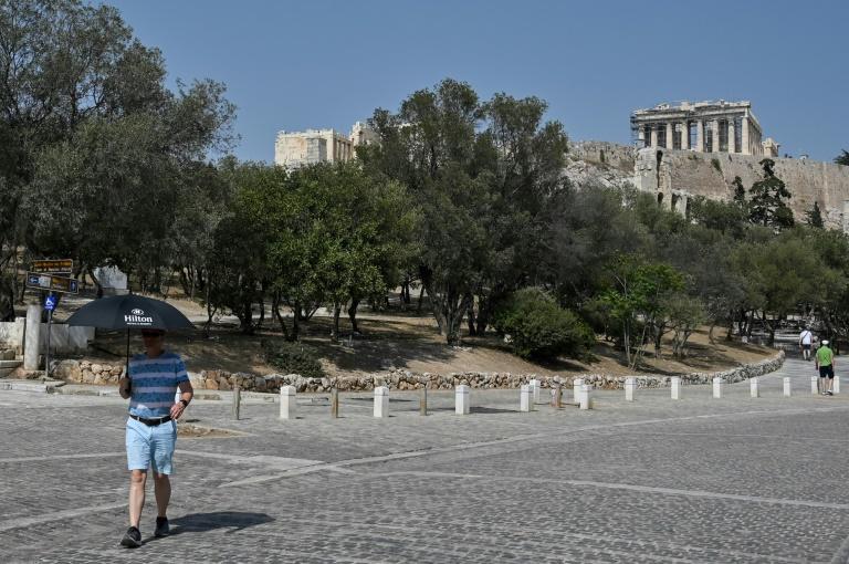 Un touriste se protège de la chaleur, au pied de l'Acropole d'Athènes, fermée aux heures les plus chaudes de la journée en raison d'une canicule exceptionnelle en Grèce, le 2 août 2021