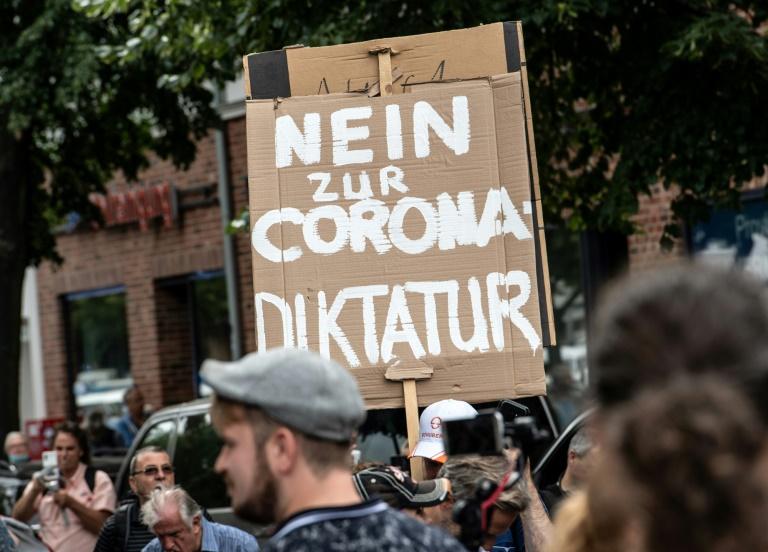 Des manifestants anti-confinement défilent à Berlin le 1er août 2021, portant une pancarte