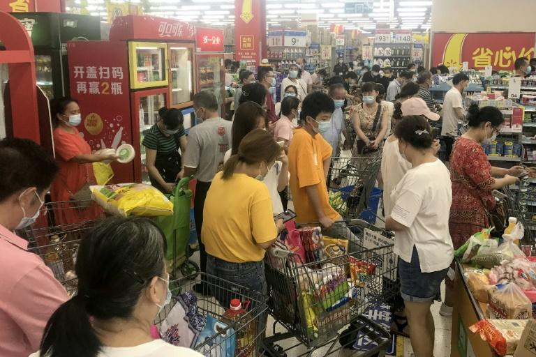 Das habitants de la ville chinoise de Wuhan font des achats dans un supermarché le 2 août 2021
