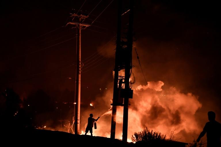 Un homme tente de lutter contre le feu avec un extincteur, le 3 août 2021 à Dekelia, au nord d'Athènes