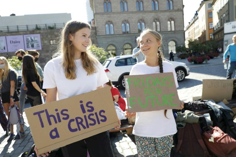 L'Allemande Luisa Neubauer (g) et la Suédoise Greta Thunberg manifestant pour le climat devant le parlement suédois, le 20 août 2021