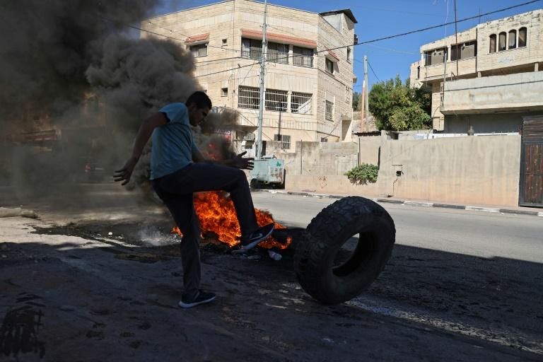 Un manifestant palestinien pousse un pneu dans une rue du village de Borqui, près de Jénine, le 26 septembre 2021 en Cisjordanie