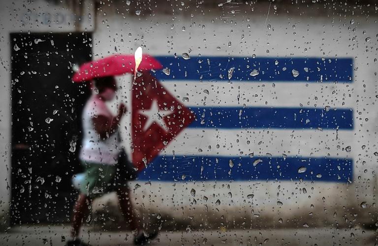 Une femme marche le long d'un mur peint du drapeau cubain à la Havane, le 12 janvier 2021
