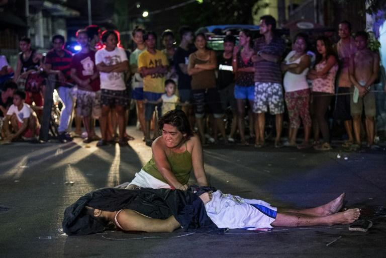 Une femme, Nanette Castillo, se tient devant le corps de son fils, Aldrin, un présumé trafiquant de drogue assassiné par des assaillants non indentifiés, à Manille, le 3 octobre 2017