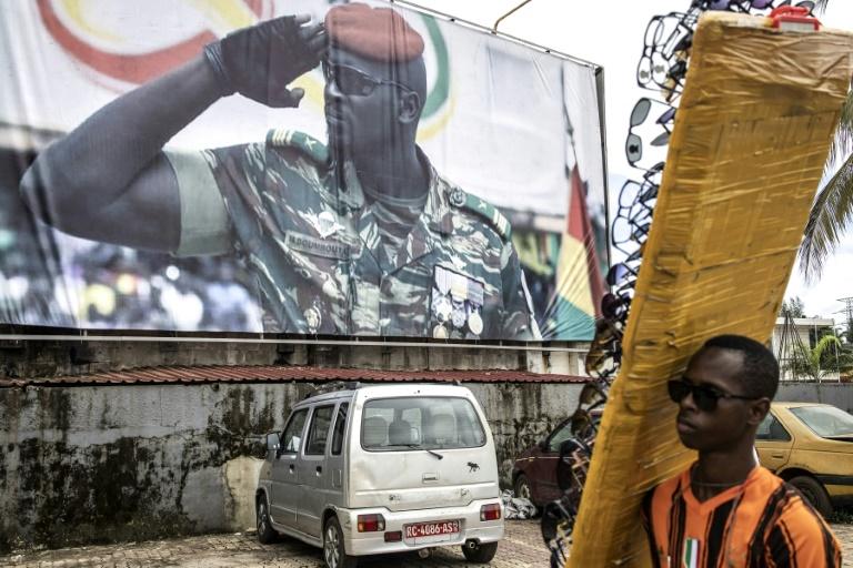 Un vendeur de lunettes passe devant l'effigie géante du colonel Mamady Doumbouya, le chef de la junte au pouvoir en Guinée, à Conakry, le 11 septembre 2021