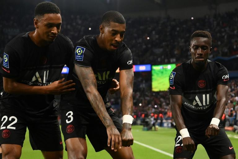 Le milieu de terrain sénégalais du Paris Saint-Germain Idrissa Gueye (d) célèbre son but contre Montpellier, avec les défenseurs Presnel Kimpembe (c) et Abou Diallo, lors de leur match de Ligue 1, le 25 septembre 2021 au Parc des Princes